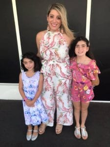 Woman standing in the middle of two children